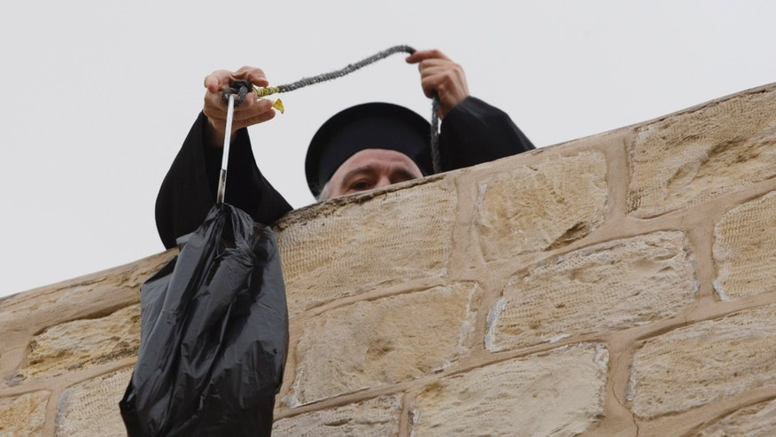 Jan. 6: Former Greek Patriarch Irineos I pulls up a bag of groceries to his apartment in the Old City of Jerusalem.