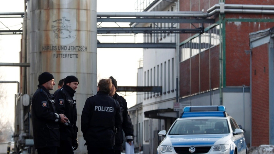 Jan. 5, 2011: In this picture, police stand in front of an animal feed products company in Uetersen, northern Germany that was searched and temporarily closed by authorities.  German authorities have stopped more than 4,700 farms from selling their meat and eggs as a precautionary measure against a growing scandal over animal feed contaminated with cancer-causing chemicals that is also affecting exports. Authorities believe some 150,000 tons of feed for poultry and swine containing industrial fat have been fed to livestock across Germany. The fat contains dioxins and should not have been in the food.