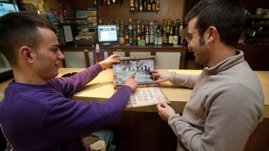 Pere Mestre, left, and Joan Bauza, right, pose pointing to their places in the calendar photo at a bar, in Sant Joan, Mallorca, Spain on Friday, Jan. 7, 2011.  Seeking to raise money for their Roman Catholic youth group on the Spanish tourist destination island of Mallorca, members came up with a risque idea: Pose nearly nude for a calendar recreating scenes from the Passion of Christ. (AP Photo/Manu Mielniezuk)