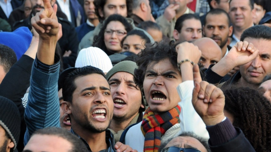 Jan. 8, 2011: People chant during a demonstration in Tunis, Tunisia, against high prices and unemployment. Witnesses say five people were injured after security forces opened fire on protesters during another street demonstration over high unemployment in central Tunisia.  One witness, a union official, says a police officer also was injured in the protest in Saida in which demonstrators set fire to tires and threw stones in the latest in three weeks of unrest. (AP)