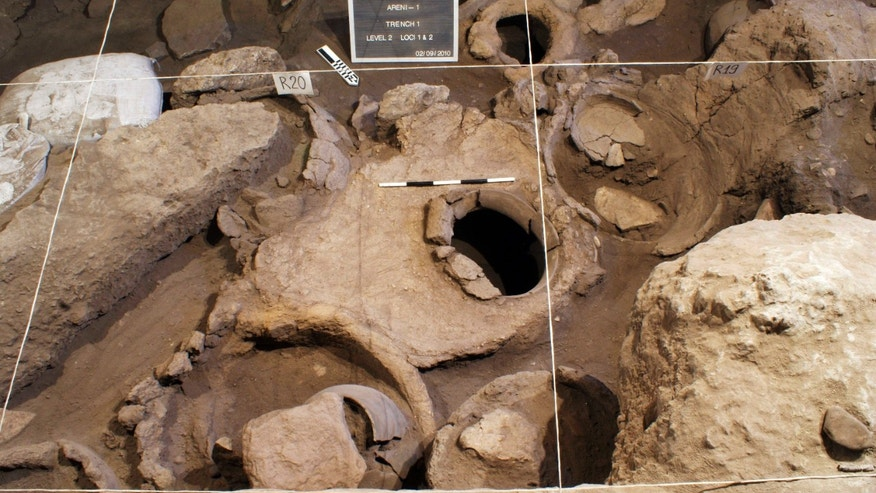 This undated handout photo provided by National Geographic shows a wine press, behind which an archaeological identification kit is placed, In Armenia. The vat, right of the press, apparently used for accumulating grape juice and the consequent wine fermentation, emerges clearly here as a result of the excavation. The earliest known wine-making equipment has been uncovered by in a cave in the mountains of Armenia. A vat to press the grapes, fermentation jars and even a cup and drinking bowl dating to about 6,000 years ago were discovered in the Areni-1 cave complex by an international team of researchers.