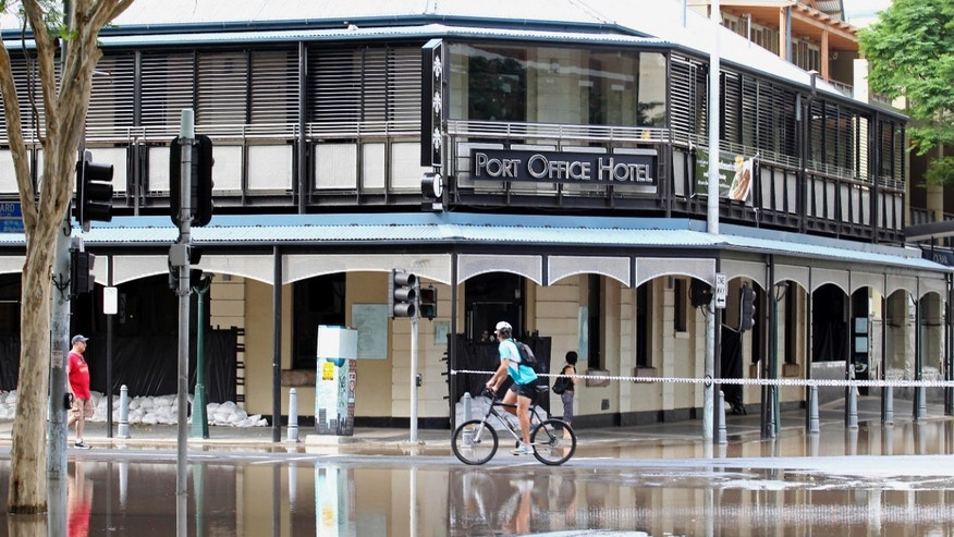 Jan. 13: A cyclist pedals past the Port Office Hotel in the city center of Brisbane, Australia.