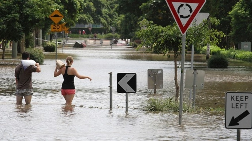 Jan. 13, 2011: Two local residents walk through floodwater after getting ice and food to take to their flooded residence in the suburb of New Farm in Brisbane, Australia