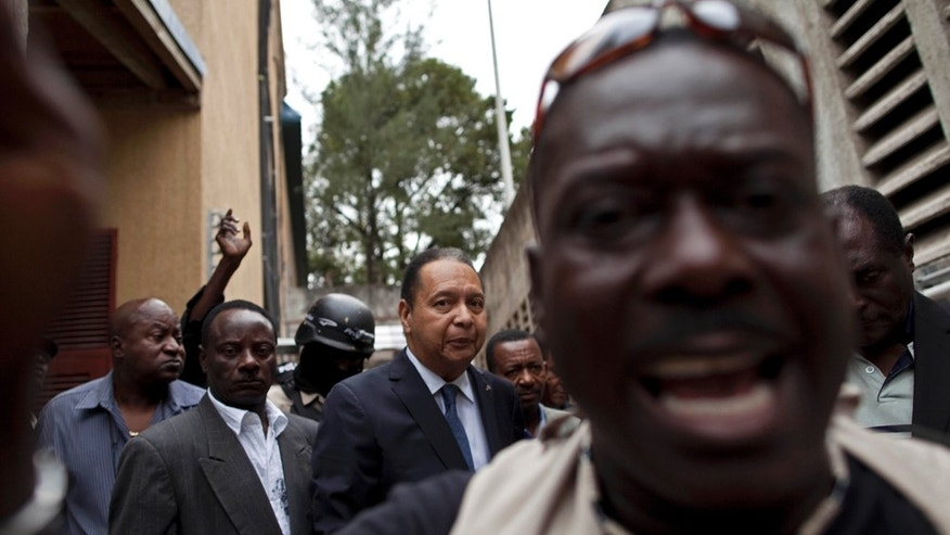 Police take Haiti's ex-dictator Jean-Claude Duvalier, center, out of his hotel in Port-au-Prince, Haiti, Tuesday Jan. 18, 2011.  Haitian police took Duvalier, who abruptly returned to Haiti on Sunday, out of his hotel to a waiting SUV without saying whether he was being detained for crimes committed under his brutal regime. (AP Photo/Ramon Espinosa)