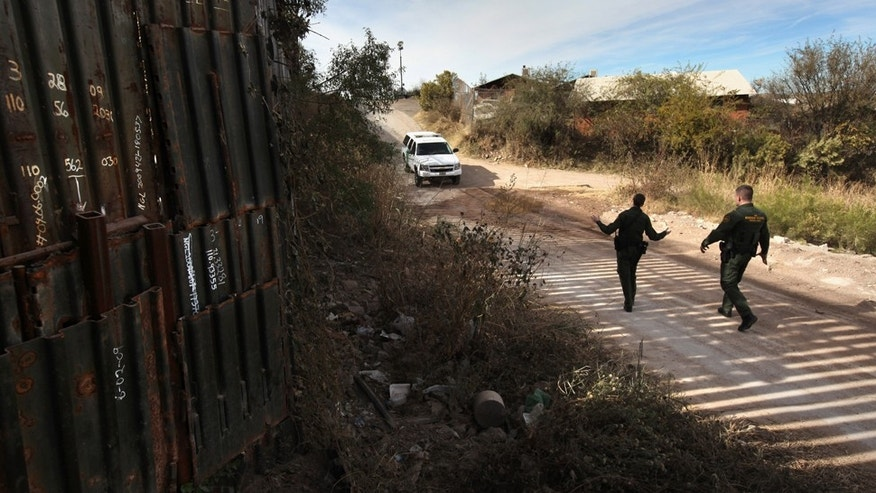 NOGALES, AZ - DECEMBER 07:  U.S. Border Patrol agents Richard Funke (R) and Colleen Agle walk along a patched section of the border fence at the U.S.- Mexico border on December 7, 2010 near Nogales, Arizona. Although a new fence has been built along the majority of Arizona's border with Mexico, critics have called for fencing of the entire stretch. Much of the unfenced terrain is in remote and mountainous areas.  (Photo by John Moore/Getty Images)