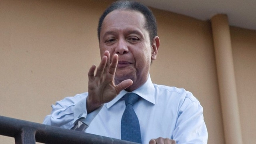 """Jan. 17: Haiti's former dictator Jean-Claude """"Baby Doc"""" Duvalier waves to the press from a hotel balcony in Port-au-Prince, Haiti."""