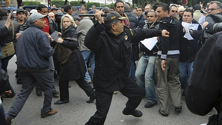 Jan. 18: A police officer faces protestors during a demonstration against the Constitutional Democratic Rally, RCD, party of Ben Ali in the center of Tunis.