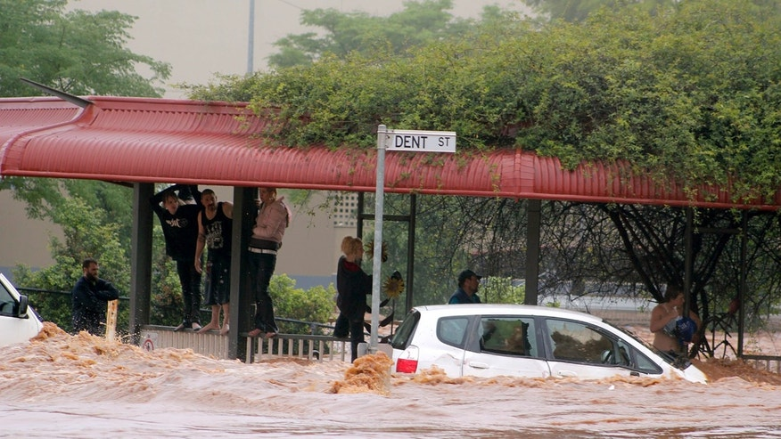 Jan. 10, 2011: People cling to railings and metal fences on a flooded street in Toowoomba, Australia, during a flash flood. Flash floods swept through the northeastern Australian community killing one woman, trapping others in cars and leaving some clinging to trees as relentless rains brought more misery to a region battling its worst flooding in decades. (AP)