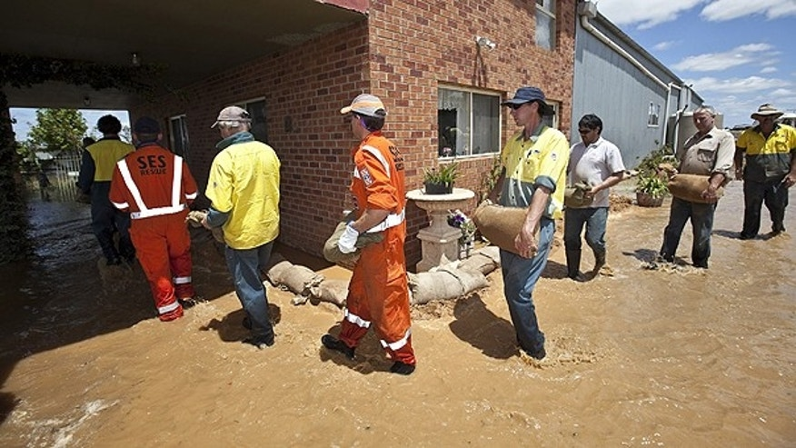 Jan. 18: In this photo provided by the State Emergency Service emergency workers and volunteers form a train to carry sandbags to be placed to protect a house from rising flood waters near Euchca, Australia.