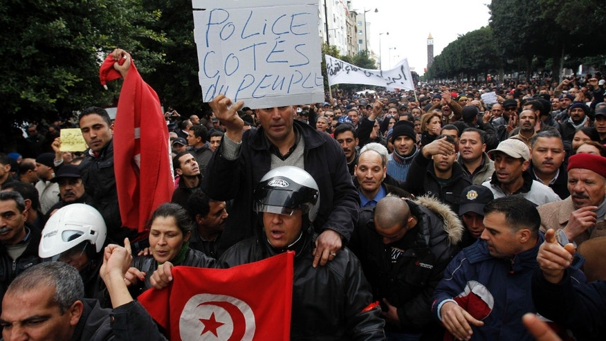 "Police officers chant slogans as they demonstrate in Tunis, Saturday, Jan. 22, 2011. Tunisia's once-feared police who carried out the repressive policies of their now exiled president are joining hands with protesters who brought down the dictator. Clusters of police guarding the daily protests on the capital's main avenue are mingling with the crowd. Placard reads "" Police with the people"""