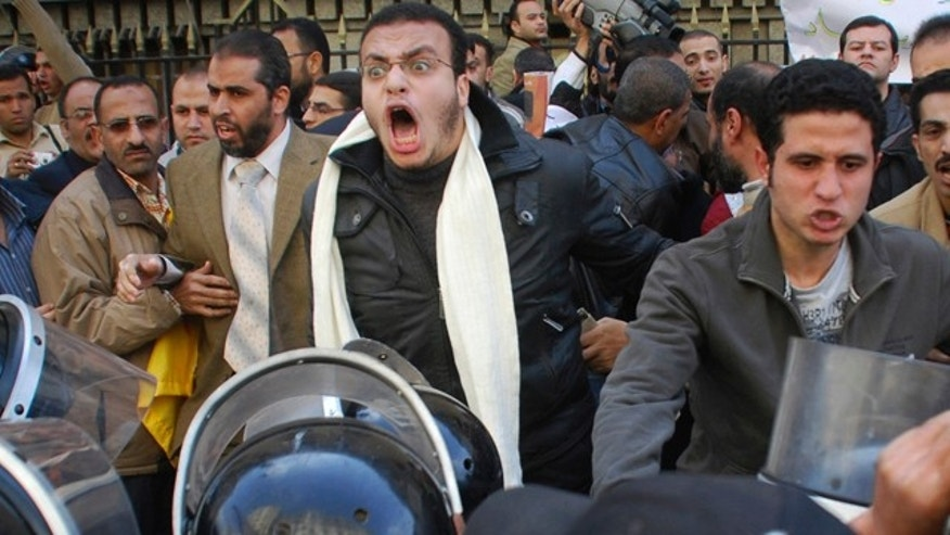 Jan. 25: Protesters are confronted by riot police as they demonstrate in downtown Cairo, Egypt.