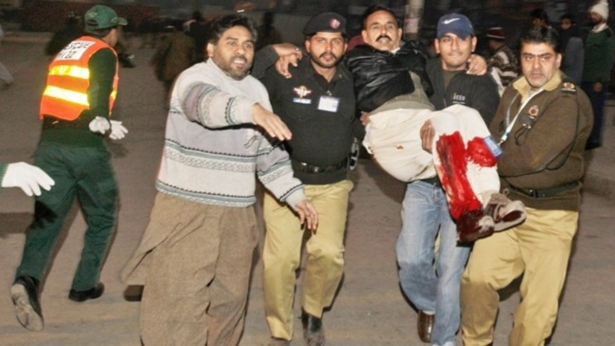 Jan. 25: Pakistani police and civilians carry an injured man from the site of a suicide bombing in Lahore, Pakistan.