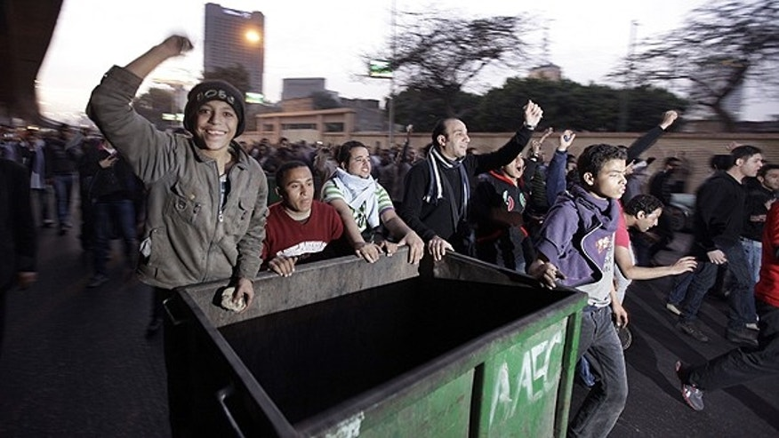 Jan. 26: Anti-government activists wheel a rubbish bin to form a barricade as they clash with Egyptian riot police in downtown Cairo, Egypt.