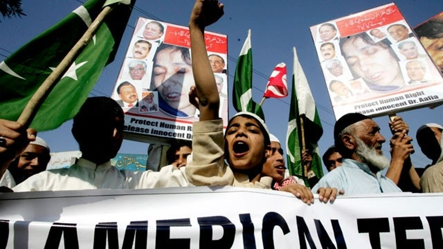 "Pakistani demonstrators shout anti-American slogans at a rally in Karachi, Pakistan, Friday Jan. 28, 2011, to protest against a U.S. consular employee, who has not been named by US authorities, suspected in the shooting of two armed men possibly intent on robbing him. Pakistan will pursue murder charges against the employee a top prosecutor said Friday. Banner on right reads ""murderer of Pakistanis and American spy should be hanged."