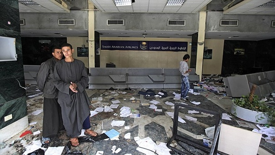 Jan. 29: People walk inside the damaged offices of Saudi Arabian Airlines, after they were looted and partially burned by anti-government protesters in Cairo, Egypt.