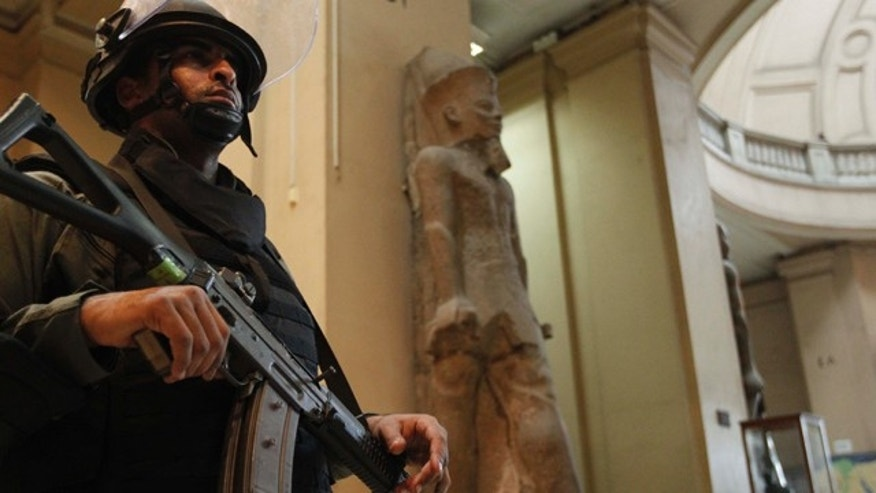 Jan. 31: A member of the Egyptian special forces stands guard on the main floor of the Egyptian Museum in Cairo, Egypt. Would-be looters broke into Cairo's famed Egyptian Museum, ripping the heads off two mummies and damaging about 75 small artifacts before being caught and detained by army soldiers, Egypt's antiquities chief said Saturday. Dr. Zahi Hawass, Director for the Supreme Council of Antiquities in Egypt, said the vandals did not manage to steal any of the museum's antiquities, and that the prized collection was now safe and under military guard. (AP)