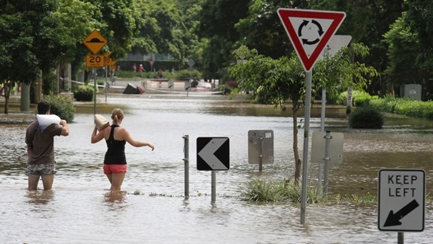 Jan. 13: Residents walk through floodwaters after getting ice and food to take to their flooded home in the suburb of New Farm in Brisbane, Australia.