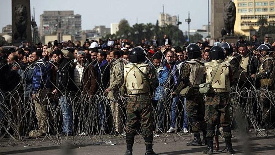 Feb. 4: Soldiers stand by as anti-government protesters line up to enter Tahrir Square, Cairo, Egypt.