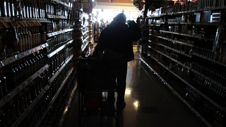 A shopper makes their way down a darkened grocery store aisle in Plano, Texas, Wednesday, Feb. 2, 2011. The cold has forced rolling blackouts across Texas.  (AP Photo/LM Otero)