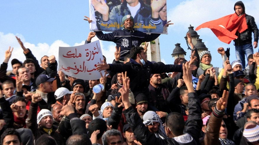 Jan. 28: Tunisian protesters demonstrate beneath a poster of slain martyr, Mohamed Bouazizi, near the prime minister's office in Tunis.