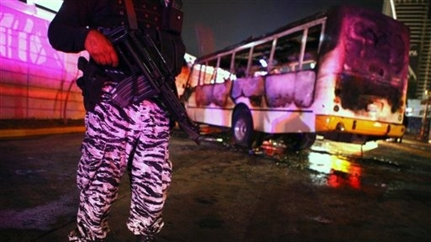 A Guadalajara state policeman stands next to a burnt-out bus on the outskirts of the city of Guadalajara, Mexico, Tuesday Feb. 1, 2011. Police are reporting gunmen set up at least 4 roadblocks and launched 2 grenade attacks in the metropolitan area of Guadalajara. No fatalities have been reported. (AP Photo/Bernardo de Niz)