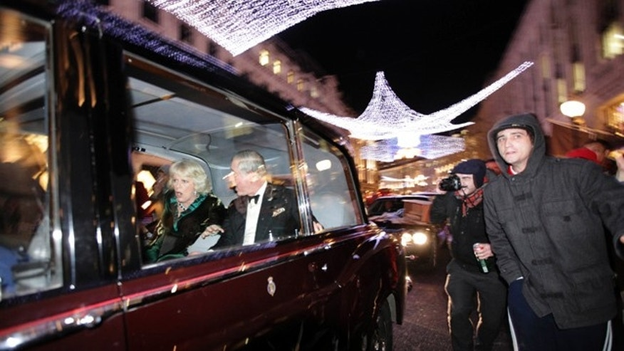 "Britain's Prince Charles and Camilla, Duchess of Cornwall react as their car is attacked, in London, Thursday, Dec. 9, 2010. Angry protesters in London have attacked a car containing Prince Charles, the heir to the British throne, and his wife Camilla, Duchess of Cornwall. An Associated Press photographer saw demonstrators kick the car in Regent Street, in the heart of London's shopping district. The car then sped off. Charles' office, Clarence House, confirmed that ""their royal highnesses' car was attacked by protesters on the way to their engagement at the London Palladium this evening, but their royal highnesses are unharmed."" ** PREMIUM RATES APPLY ** (AP Photo/Matt Dunham)"
