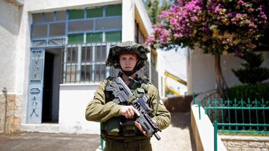 Aug. 5, 2009:  An Israeli soldier stands guard in Ghajar, which is located between northern Israel and Lebanon. Political turmoil has delayed Israeli plans to pull out of the village