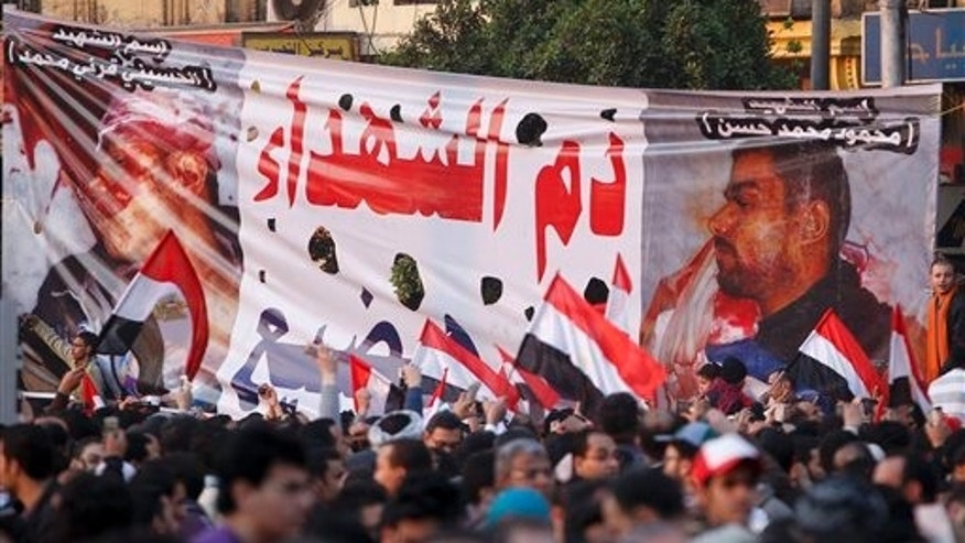 "Feb. 8: A large banner depicting people who were killed during clashes and the Arabic writing reading ""The blood of the martyrs"" is seen in Tahrir Square, in Cairo, Egypt. Faces of some of the hundreds killed in Egypt's two-week-old uprising are beginning to emerge from the fog of chaos. (AP)"