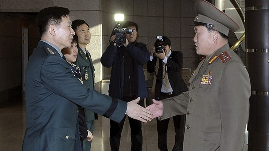 Feb. 9: In this photo released by the Defense Ministry, North Korean Army Col. Ri Sun Gyun, right, shakes hands with South Korean counterpart Col. Moon Sang-gyun upon his arrival for their military meeting at the south side of the truce village of Panmunjom in the demilitarized zone.