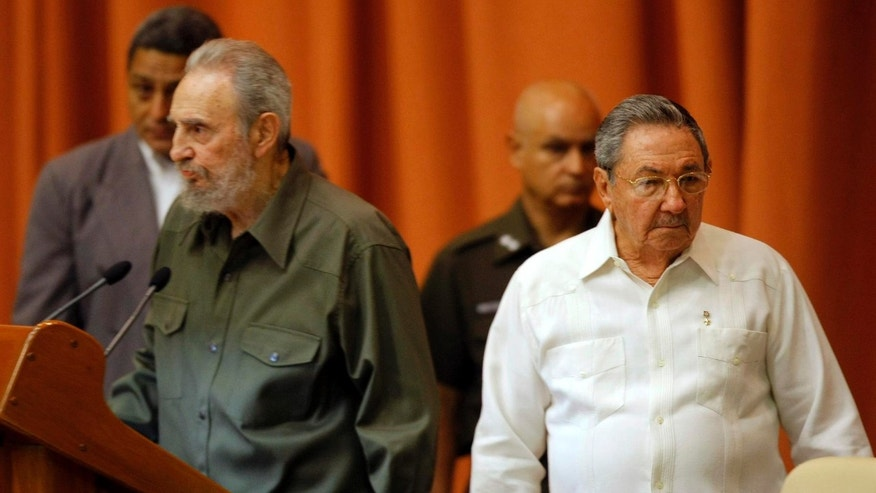 Fidel Castro, left, and his brother Raul Castro attend a special session of parliament in this 2010 file photo.