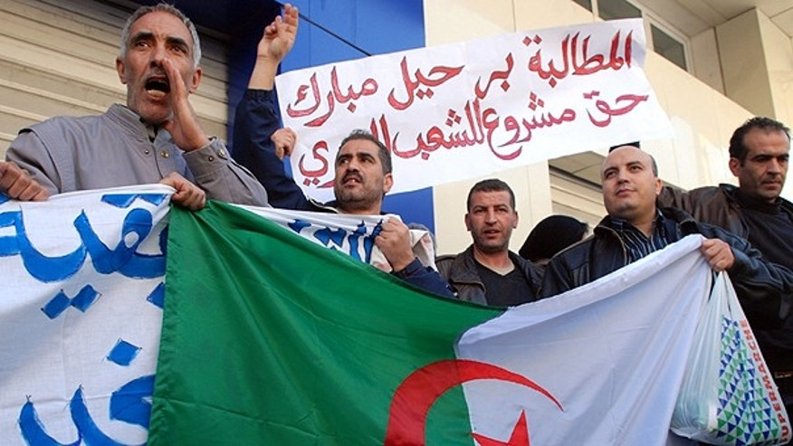 Feb. 9: Protesters hold an Algerian flag as they chant slogans outside the Egyptian embassy during a demonstration against Egyptian President Hosni Mubarak, in Algiers, Algieria.