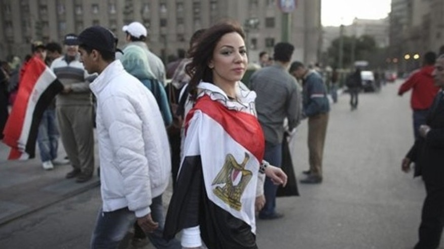 Feb. 13, 2011: A woman wearing an Egyptian flag walks into Tahrir Square, in Cairo, Egypt
