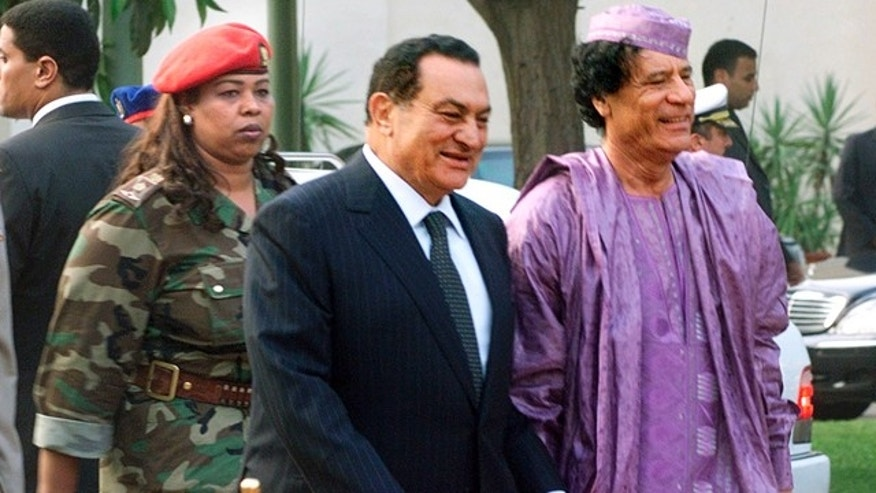 This July 21, 2002, file photo shows Egyptian President Hosni Mubarak, center, welcoming Libyan leader Moammar Gadhafi, right, who is guarded by a female bodyguard, left, upon his arrival at the Presidential Palace in Cairo.