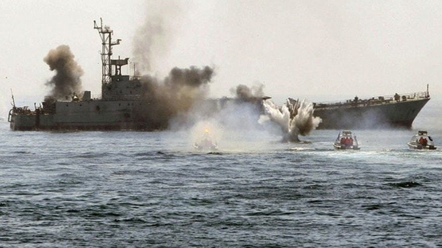 An Iranian warship and speed boats take part in a naval war game in the Persian Gulf and the Strait of Hormuz, southern Iran on April 22, 2010.