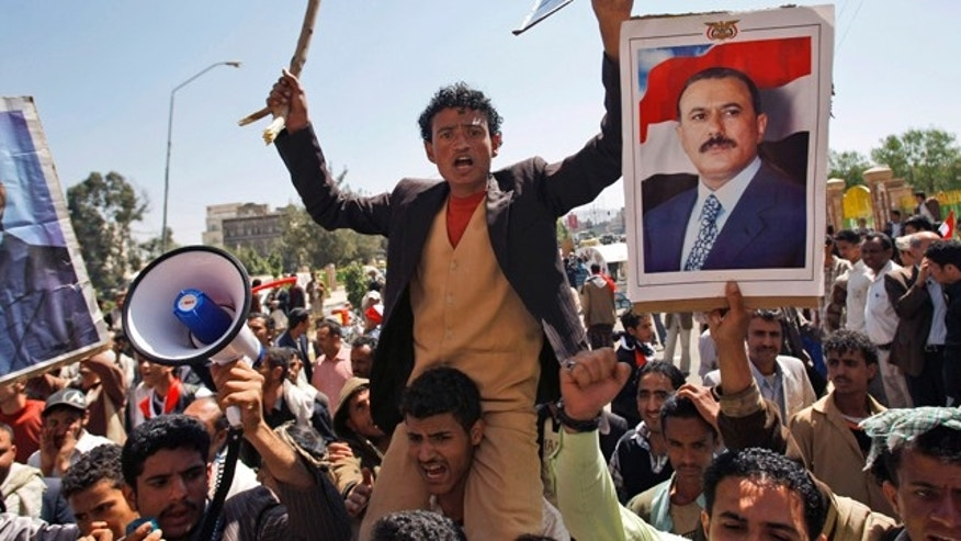 Feb. 16: Supporters of the Yemeni government shout slogans as they try to enter Sanaa University where anti-government protestors gather, in Sanaa, Yemen.