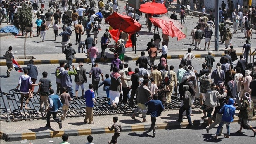 Feb. 17: Supporters of the Yemeni government, below, chase after anti-government demonstrators, top, during clashes in Sanaa, Yemen.