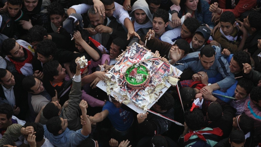Demonstrators grab pieces of a cake as it is passed above their heads during a rally in Tahrir Square in Cairo, Egypt, Friday Feb. 18, 2011. Some thousands of flag-waving Egyptians packed into Tahrir Square for a day of prayer and celebration Friday to mark the fall of longtime leader Hosni Mubarak a week ago and to maintain pressure on the new military rulers to steer the country toward democratic reforms.