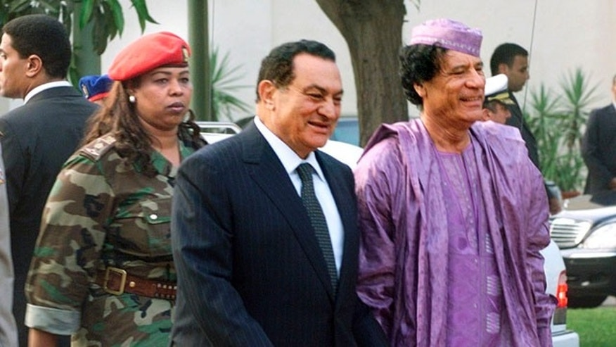 FILE: This July 21, 2002 file photo shows Egyptian President Hosni Mubarak, center, welcoming Libyan leader Moammar Gadhafi, right, who is guarded by a female bodyguard, left, upon his arrival at the Presidential Palace in Cairo.