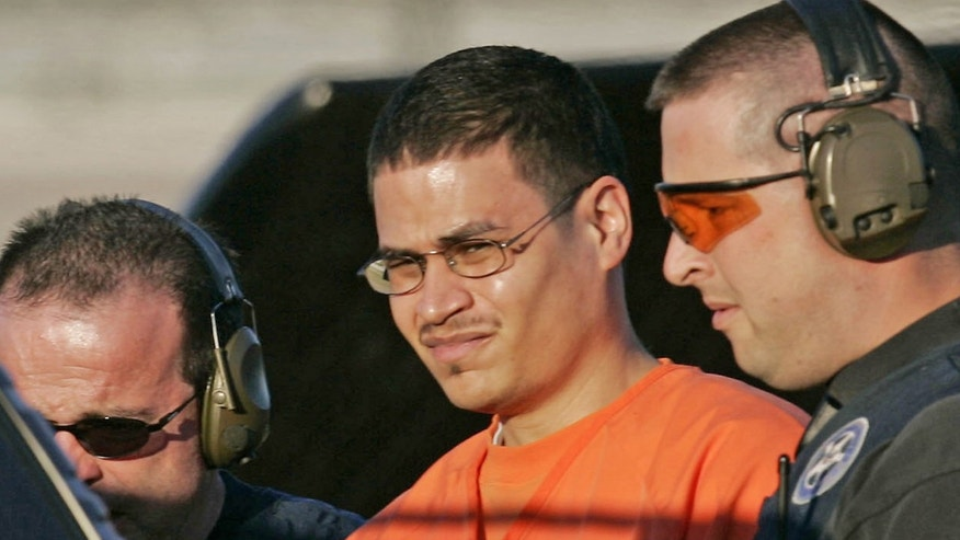 "Jose Padilla, center, an alleged al-Qaida operative held as an ""enemy combatant"" for more than three years, is escorted to a waiting police vechicle by federal marshals near downtown Miami Thursday, Jan. 5, 2006 as he arrives to face terrorism charges. (AP Photo/J. Pat Carter)"