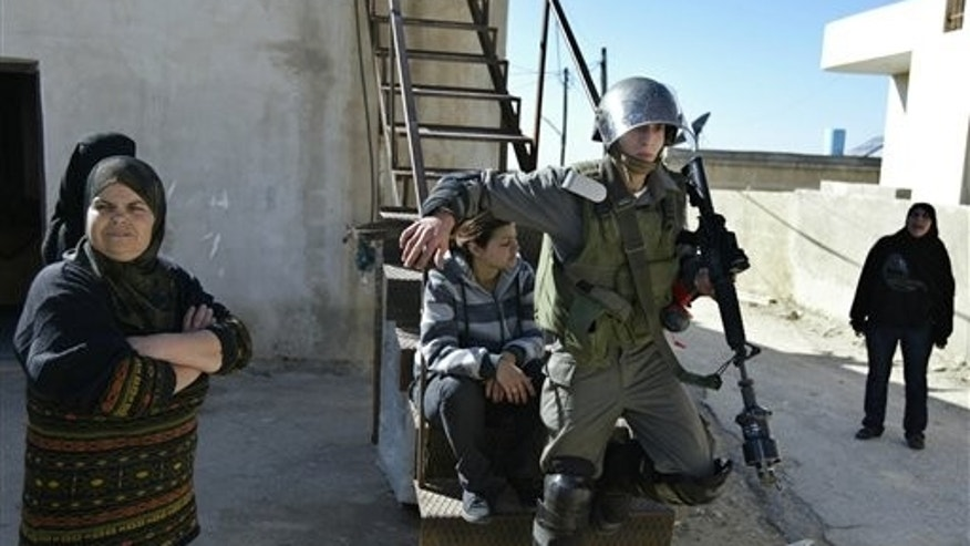 Feb. 18, 2011: An Israeli border police officer walks out from a Palestinian house during clashes with Palestinian demonstrators during a protest against the expansion of the nearby Jewish settlement of Halamish in the West Bank village of Nabi Saleh.