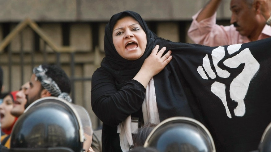 April 13, 2010: Opposition protesters demonstrate with a clenched fist on a black flag behind a cordon of security forces in downtown Cairo, Egypt.