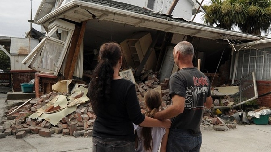Feb. 26: Maree, left, daughter Jasmine, center, and Norm Butcher take a last look at their destroyed home in Christchurch, New Zealand.