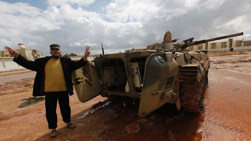 Feb. 24, 2011: A Libyan man flashes a V sign next to a destroyed tank at Al-Katiba military base after it fell to anti-Libyan leader Moammar Gadhafi protesters a few days ago