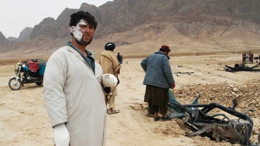 Feb. 27, 2011: A wounded Afghan man looks on as others examine the wreckage of a car after an explosion in the Arghandab district of Kandahar province, Afghanistan.