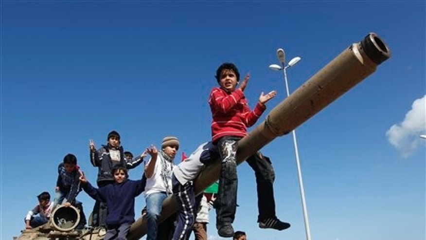 Feb. 28, 2011: Libyan boys sitting on the cannon of a destroyed army tank celebrate the freedom of Benghazi, Libya.