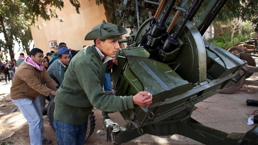 March 1, 2011: New Libyan rebel recruits from the forces against Libyan leader Muammar al-Qaddafi push an anti-aircraft gun at a military base in Benghazi, eastern Libya.