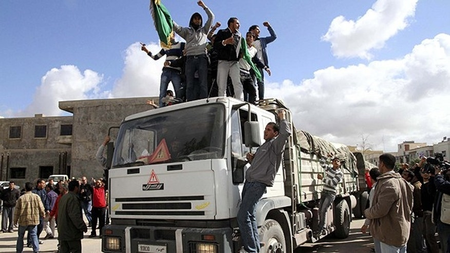 March 1: In this photo released by China's Xinhua News Agency, supporters of Libyan leader Muammar al-Qaddafi shout slogans on top of a truck of an aid convoy in the town of Qasr bin Ghashir, south of Tripoli.