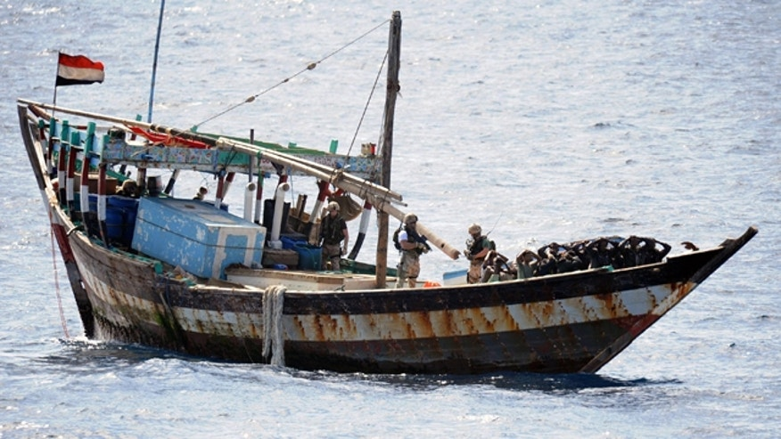 In this image made available by the Ministry of Defense in London, Thursday Feb. 16, 2011, a naval boarding party from HMS Cornwall guard Somali pirates after their dhow was boarded in the Indian Ocean on Thursday Feb. 10, 2011.