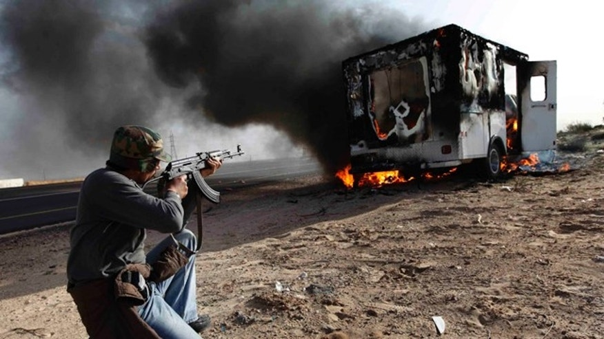 March 2, 2011: A Libyan rebel shoots towards a burning pro-Muammar Qaddafi fighters' vehicle in celebration of them retaking the town of Brega, east of Libya. Regime opponents battled forces loyal to Libyan leader Muammar Qaddafi who tried Wednesday to retake a key oil installation in a counteroffensive against the rebel-held eastern half of the country.