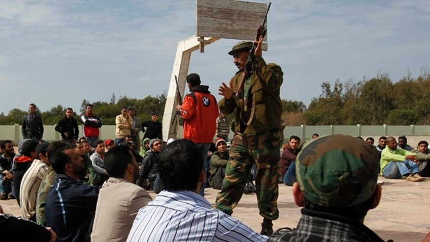 March 3: A former Libyan army soldier shows new Libyan rebel recruits how to use the AK-47, during a training session after signing up with the forces against Libyan leader Muammar al-Qaddafi at a training base in Benghazi, eastern Libya.